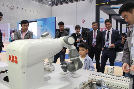在展区,ABB双臂机器人YuMi与工人协作完成装配任务